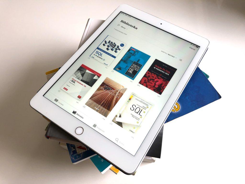 Stos książek i tablet z zainstalowaną biblioteką ebooków